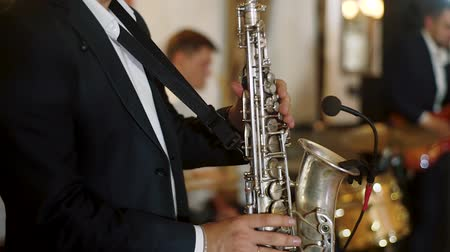 saxofon : Musician wearing black suit plays saxophone on scene. Saxophonist play on golden saxophone with microphone. Jazz band playing on background.