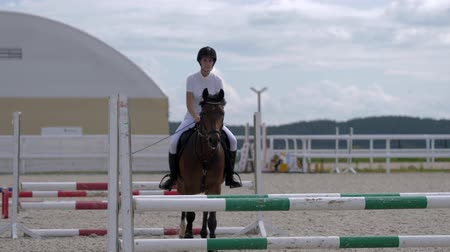 barreira : Horsegirl riding strong brown horse jumping over obstacles in outdoors sandy parkour riding arena. Female equestrian rider running on stallion at show jumping competition. Close up, slow motion. Vídeos