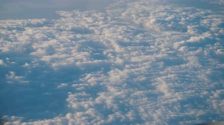 soft earth : Flying over cumulus clouds. View from the airplane window. Heavenly beautiful cloud scape, clear blue sky. Dense fluffy clouds softly lit by the sun. 4k video