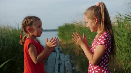 Two little cute girls playing patty cake game, having fun on wooden boards by the lake. Two children playing a clapping hands game. Close up, slow motion. Stock mozgókép