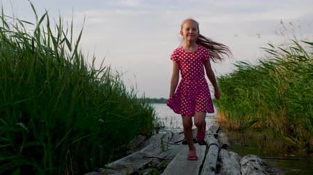 Happy little girl in a red polka dot dress runs between thickets of reeds on wooden boards from the lake. Childhood, freedom. Steadycam shot, slow motion.