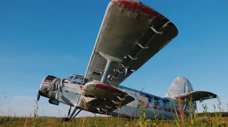 letec : Currently unused aircraft being standing in the field against clear blue sky. Abandoned old small propeller plane. Airplane graveyard. Details of metal exterior of airplane sways in the wind.