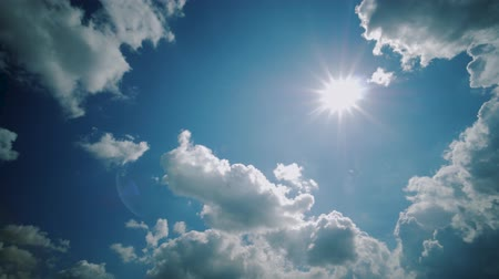 distante : Clouds moving in clear blue sky background, sun shines through clouds, sunny day timelapse.
