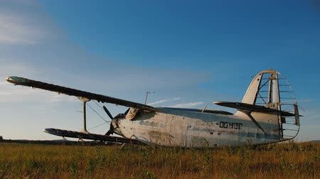 hanyatlás : Currently unused aircraft being standing in the field against clear blue sky. Abandoned awning old small propeller plane. Airplane graveyard.