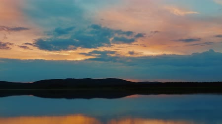 Dramatic colorful timelapse of sunset. Beautiful fiery cloudy sky moving over lake. Stock mozgókép