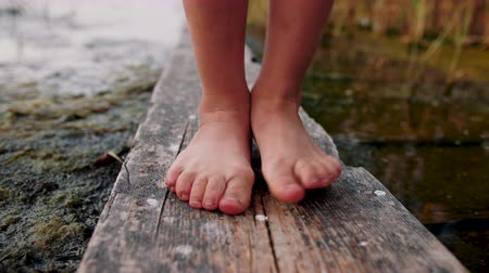 zavřít : Little girl feet stand on wooden plank and toes move. In the background of lake. Close up.