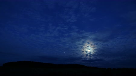 nazomer : Timelapse: mysterious moon hiding behind clouds, shining brightly in dark night sky. Moonlight shines in navy blue night sky, clouds are moving, lights of planes fly through it.