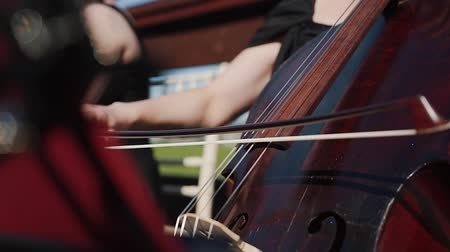 Female hand plays cello with bow, close up. Outdoor orchestra, musicians playing string instruments.