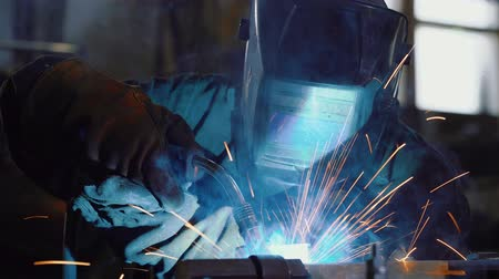 nowoczesne : Close up: worker in face shield or protective mask uses gas welding torch to connect the seam of metal part in industrial factory. Blue fire flickers, orange sparks are flying, blacksmith manual work.