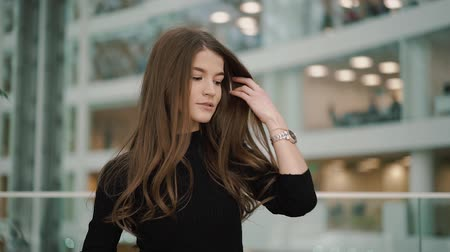 glamourous : Attractive young woman with brown eyes, long hair, with nails French manicure, with watches in black turtleneck looks to camera, touch her hair, gives a lovely playful smile. Slow motion Stock Footage