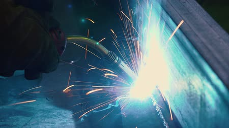 kaynakçı : Close up of gas burner flame. Worker uses a gas welding torch to connect the seam of the metal part on industrial factory. Blue fire flickers, and orange sparks are flying and glowing.
