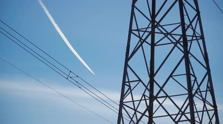 Close up: high voltage power transmission tower and electricity pylon against blue sky. Airplane with white trail or trace on the blue sky. Archivo de Video