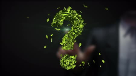 Businessman touching green question mark made from leaves. (Included alpha)