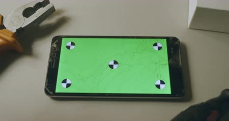 repairer : Checking phone with broken screen, fixing, smartphone with green screen