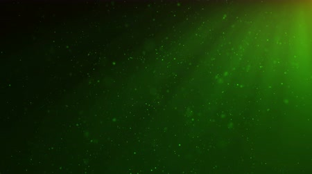 Abstract motion background of shining, sparkling, green particles. Beautiful green floating dust particles with shine light. Seamless Loopable 3D. 4K Animation