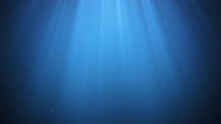 Rays of sunlight shining from above penetrate deep clear blue water. Sun light beams underwater. Small bubbles move up, under the water surface. Seamless Loop-able 3D Animation. 4K