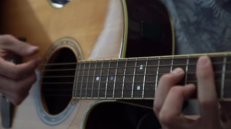 hmatník : Guitarist playing acoustic guitar in studio - selective focus close-up of the fingerboard and hand playing rock pop chords