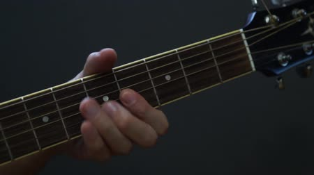 akusztikus : Guitarist playing acoustic guitar in studio - selective focus close-up of the fingerboard and hand playing rock pop chords