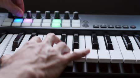 yüksek sesle : Musician playing MIDI keyboard    MIDI controller synthesizer in studio - selective -focused piano keys closeup for electronic music production  recording