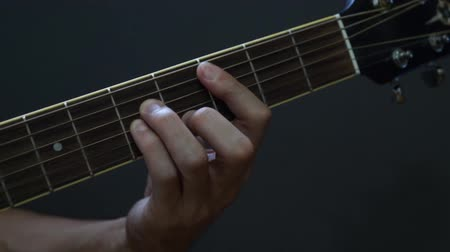 özel öğretmen : Guitarist playing acoustic guitar in studio - selective focus close-up of the fingerboard and hand playing rock pop chords