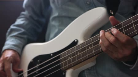 nejlon : musician playing bass guitar finger style in studio, closeup with selective focus - musical instruments - concept musical composition and creativity