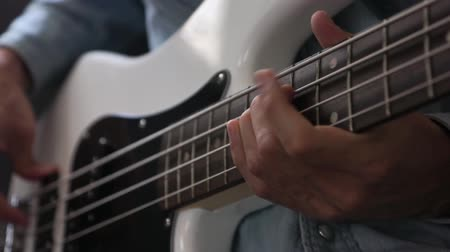 skladatel : musician playing bass guitar finger style in studio, closeup with selective focus - musical instruments - concept musical composition and creativity
