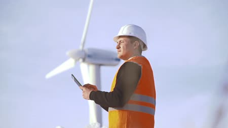 elektrownia wiatrowa : Energy Engineer of the windmill to work with the tablet at sunset. environmental