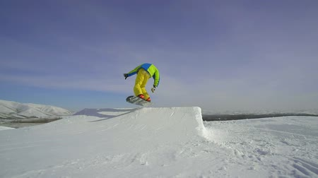 wandering : man skiing snowboarder makes a jump freeride in the ski resort