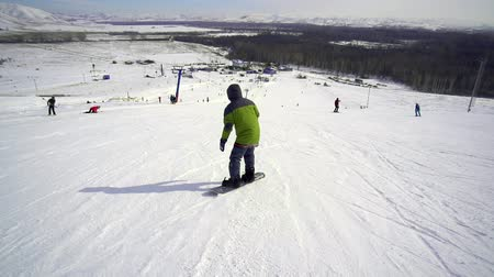 snowboard : skiing man descends on a snowboard in sunny weather on a snowy slope Wideo