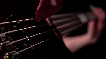 slapping : Musician playing five string electric bass guitar macro