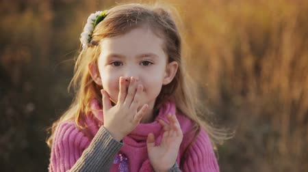 beijos : little girl in a sunset light blows a kiss to the camera