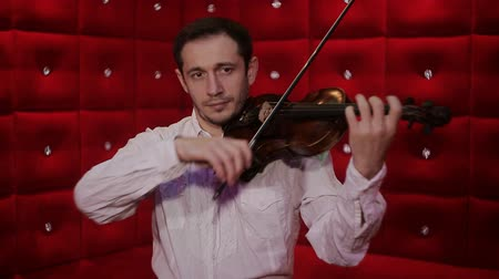 houslista : Violinist playing in red background.