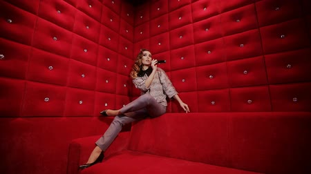 pinup : A elegant girl is sat on the edge of a vintage red sofa and is singing karaoke Stock Footage