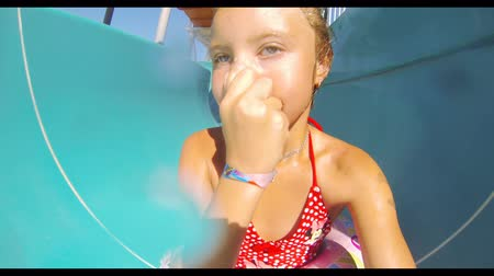 kaluž : Child sliding down water slide in pool. Close up