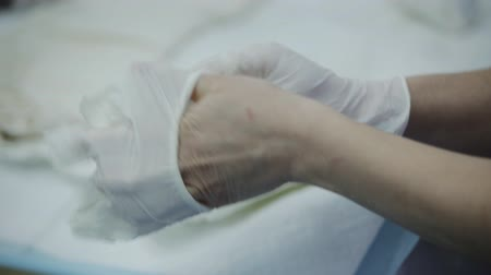 traumatic : Female surgeon putting on gloves in operating room