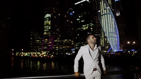 panoramic view : brutal man in a white suit in the night Business Center