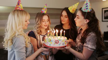 aprósütemény : girlfriend to birthday girl blows out the candles on the cake