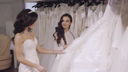 подвенечное платье : seller consultant helps the bride to choose a wedding dress in a trendy salon