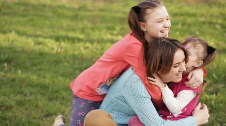сестра : Mom having fun playing with daughters in the summer park on the grass