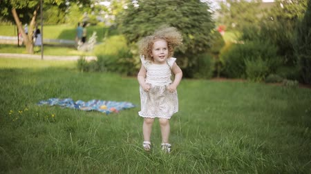 yards : curly girl in a summer Park jumps Stock Footage