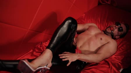 itaatkâr : The male stripper in womens shoes, with a gag in his mouth is in the red room