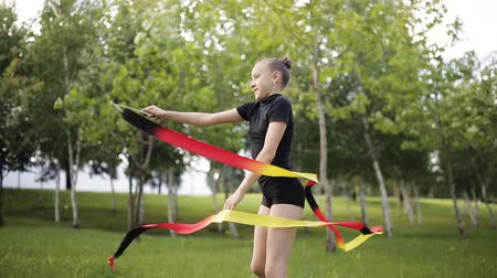 gymnasta : A young gymnast with ribbon performs exercises in the Park. Dostupné videozáznamy