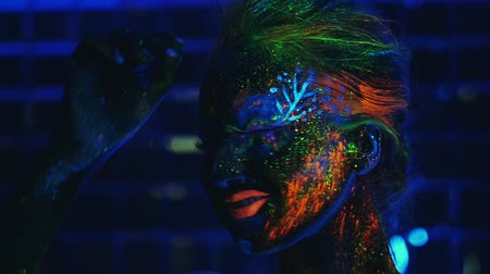 multicor : young girl painted fluorescent powder , laughing in ultraviolet light