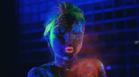 luxúria : girl in ultraviolet light blows pink fluorescent powder with palm