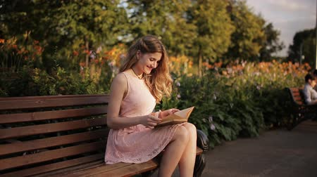 bank : beautiful young blond woman sitting on a bench in the summer park and reading a book