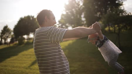 detém : young happy dad turns his little daughter in a park at sunset
