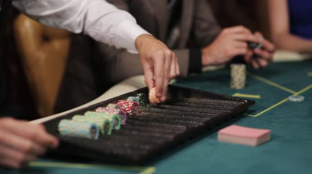 risco : The dealer at the poker table lays chips under par