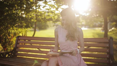 enciclopédia : Young woman sitting on the bench in a park and reading a book. Beautiful european girl studying a subject with book