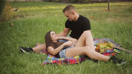 otuzlu yıllar : Beautiful Young Couple Having Picnic in Countryside. Happy Family Outdoor. Smiling Man and Woman relaxing in Park. Relationships Stok Video