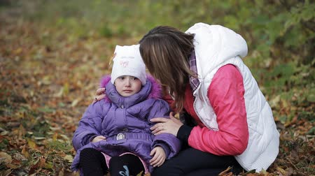 átölelő : The little girl crying in autumn park. Mother comforting a crying child. Tears on the cheeks